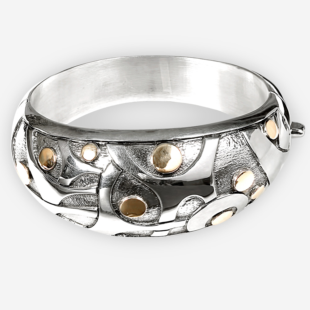 Silver bangle with blackened sterling silver and an embossed motif of abstract dancing little men with embossed14k gold heads.