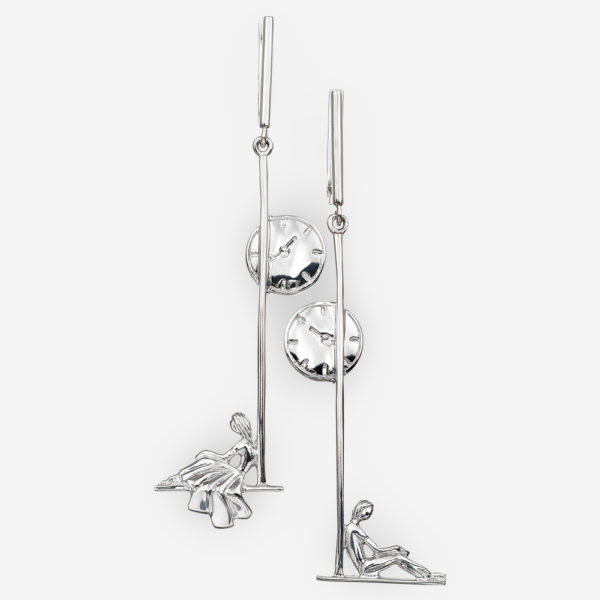 Asymmetrical silver earrings depicting a romantic couple sitting under a street clock.