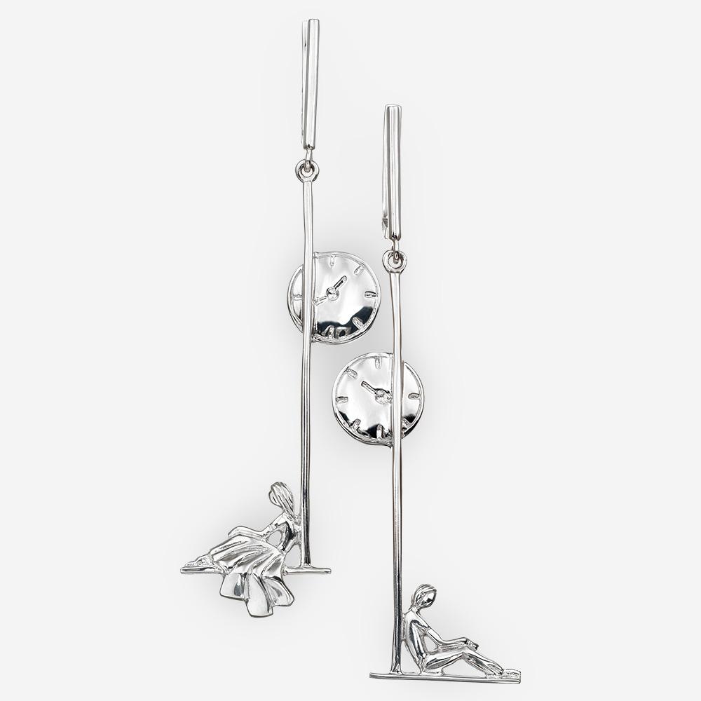 Aretes de plata asimétrica pareja romántica sentados bajo reloj de la calle.