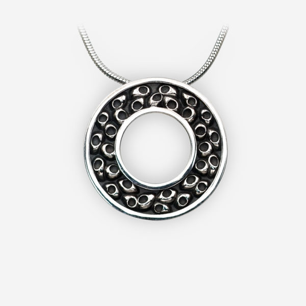 Blackened sterling silver round pendant with an embossed pattern.