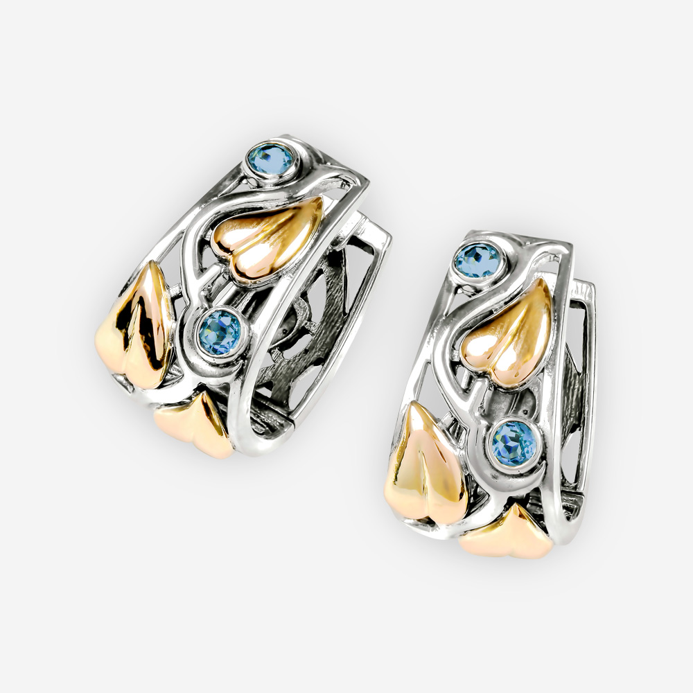 Blue topaz two tone earrings with golden leaves and huggie closures.