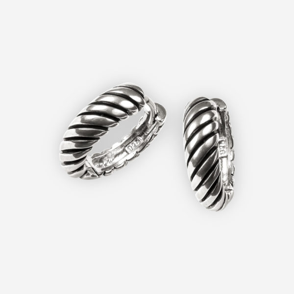 Classic silver hoop earrings are crafted with a twisted cable design and have a huggie closure.