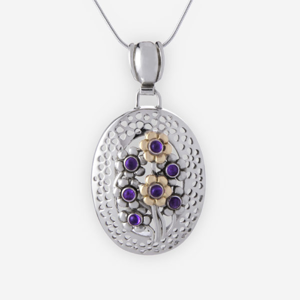 Domed oval floral pendant is crafted from 925 sterling silver and 14k gold with flower details and amethyst cabochons.