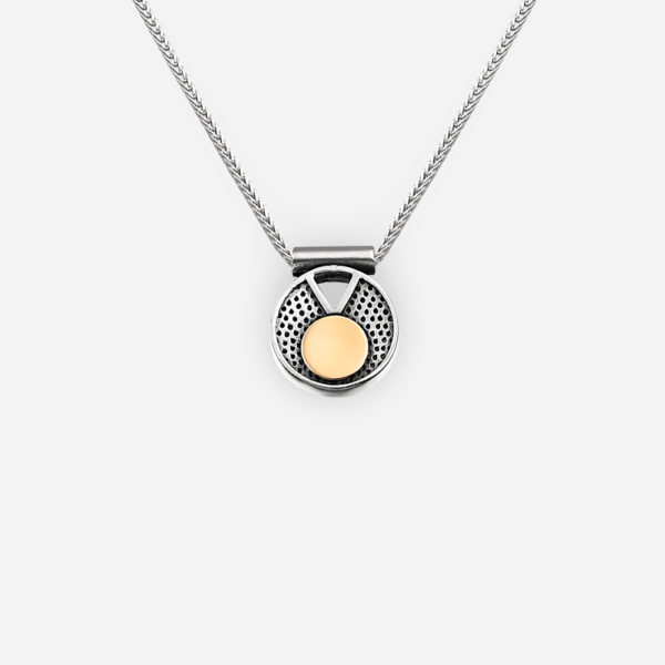 Modern two tone silver necklace with geometric cut out design and gold accents on a silver chain.