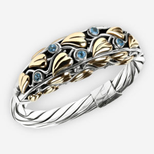 Ornate silver bangle with 14k gold leaves and blue topaz gemstones.