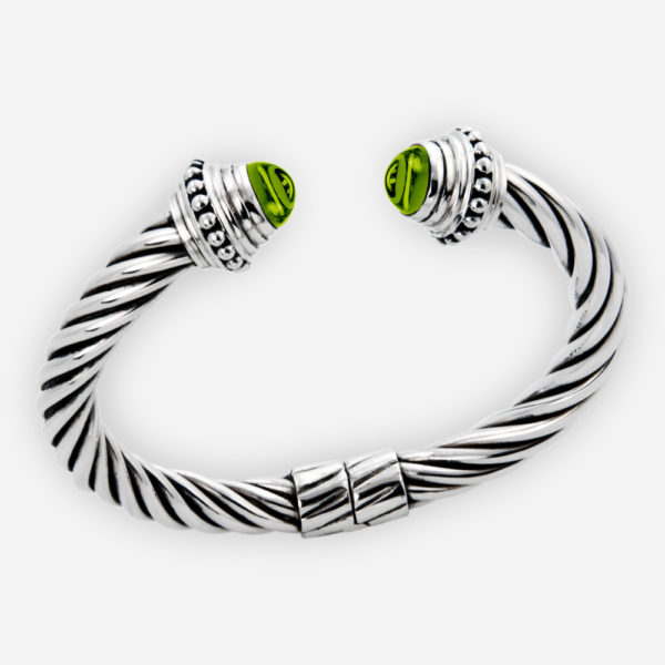 Peridot cabochon twisted cable bangle features a sterling silver twisted cable design and two peridot cabochons.