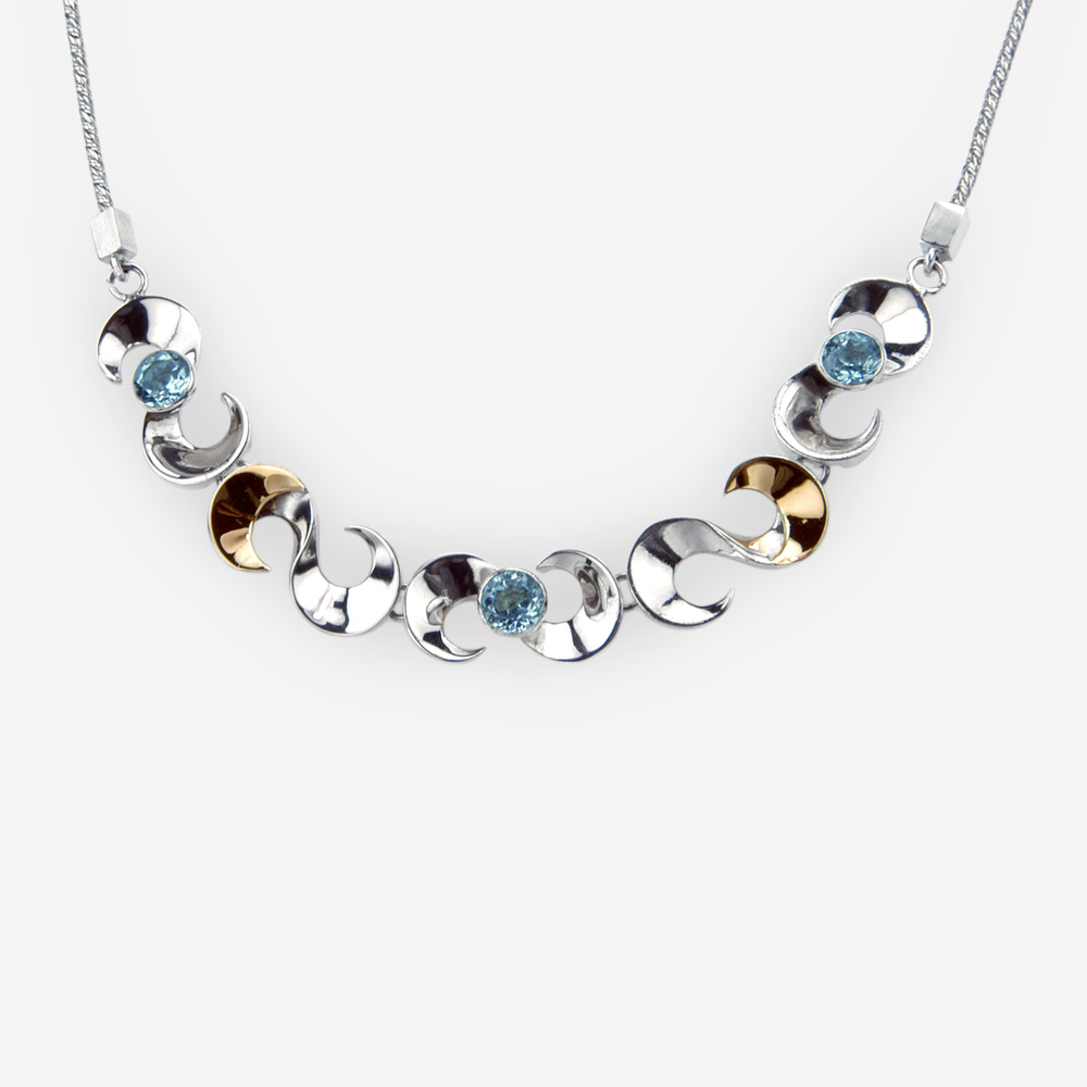 Scrolling silver link necklace is crafted from 925 sterling silver, 14k gold accents, faceted gemstones, and a sterling silver chain.