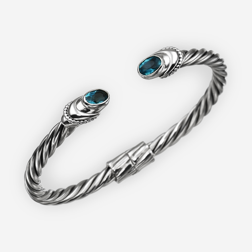Pulsera de plata fina de cable torcido con zirconia cúbica azul.