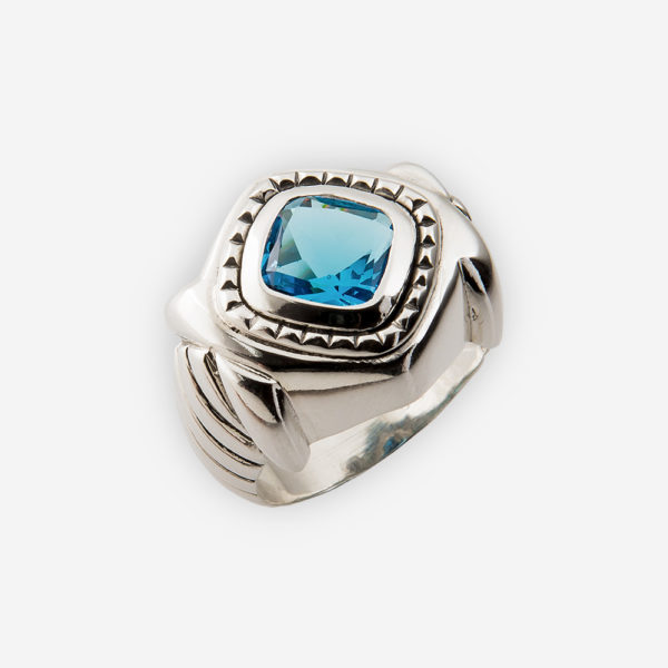 Sterling silver cocktail ring with ornate carved details, faceted blue cz stone and silver bezel.