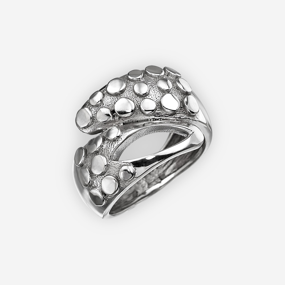 Modern silver statement ring with a cut out design and polished sterling silver embossed dots on a sterling silver background.