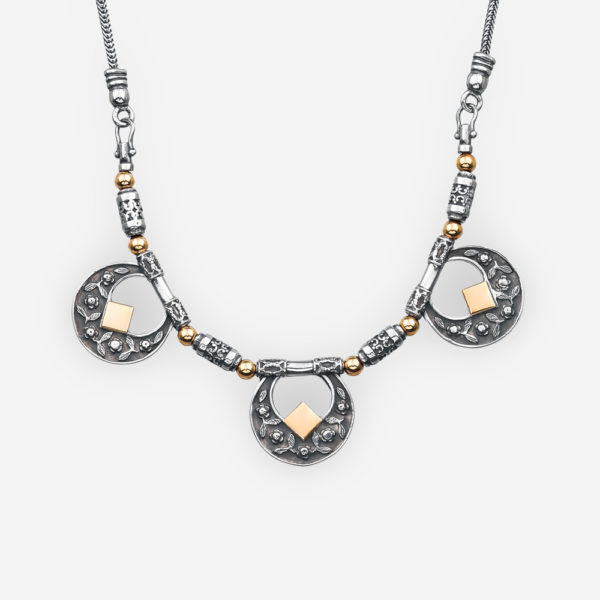 silver floral medallion necklace has an oxidized finish and made from 925 sterling silver and 14k gold.