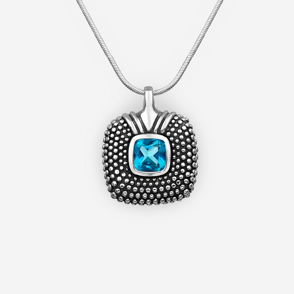 Pendiente de plata cuadrado con pequeños puntos de plata y un zirconia cúbica azul facetado.