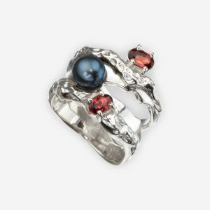 Sterling silver Art Deco ring set with a black freshwater pearl and two garnet gems.