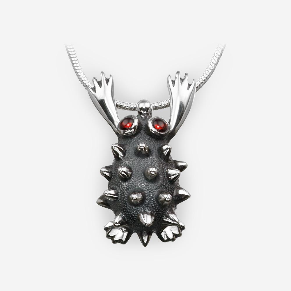 Pendiente de erizo de plata con ojos de granate.