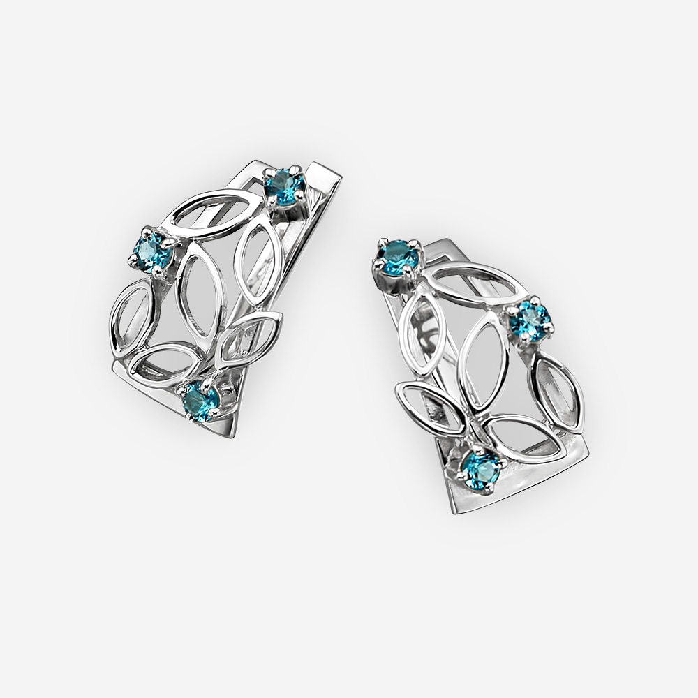 Sterling silver openwork earrings set with blue topaz gemstones.