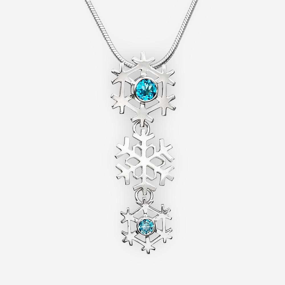 Pendiente de copo de nieve de plata con piedras preciosas de topacio azul.