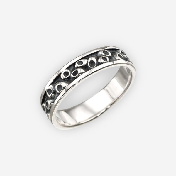 Thin oxidized sterling silver ring with small round embossed design.