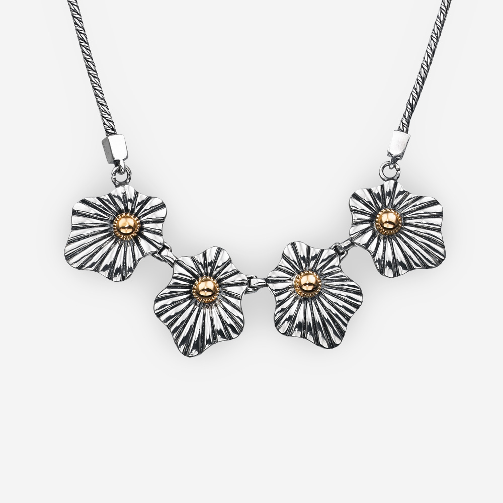Two tone silver floral necklace and 14k gold accents on a rope chain.