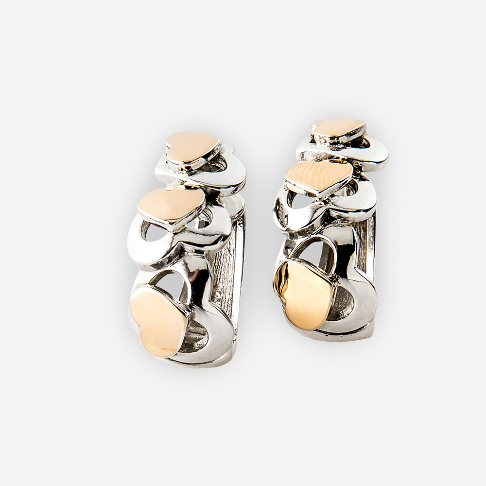 Two tone silver heart earrings. Huggie style with cutout heart design and overlapping gold hearts.
