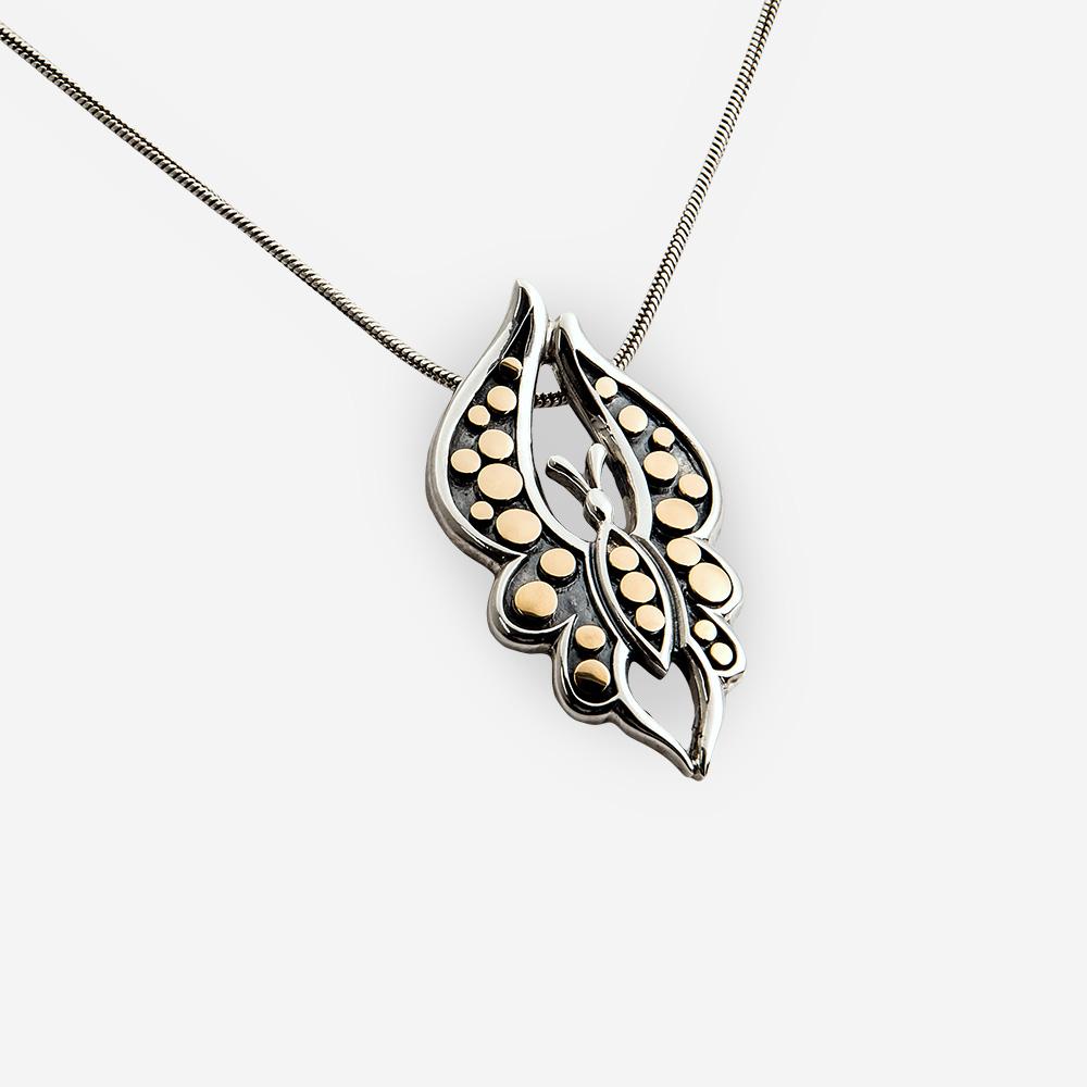 Esta pieza se convierte en colgante y broche. Tiene forma de mariposa y esta hecha de plata oxidada .925  con incrustaciones de oro fino de 14 kt.