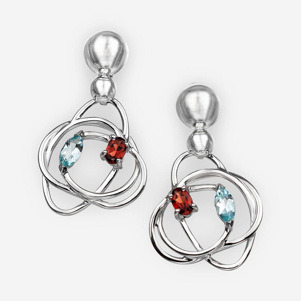 Unique silver earrings with swirling pendants and set with blue topaz and garnets.